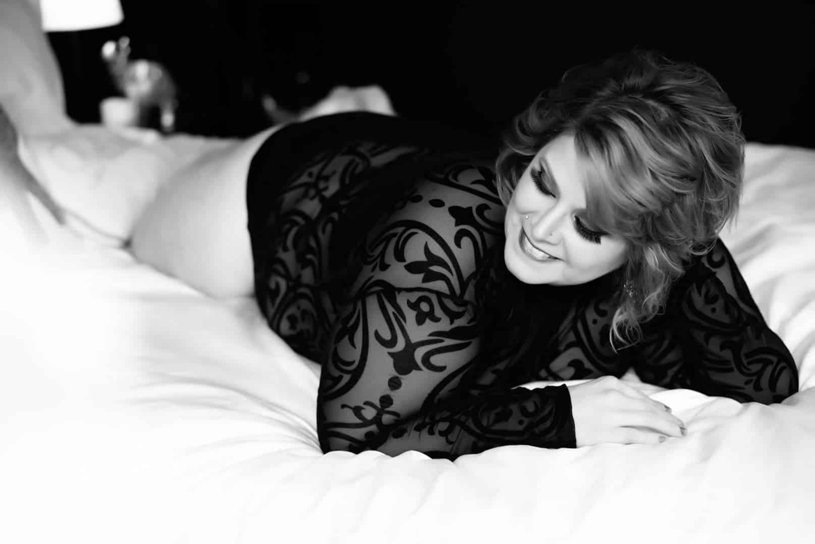 Woman posing in black long sleeved lingerie on a bed