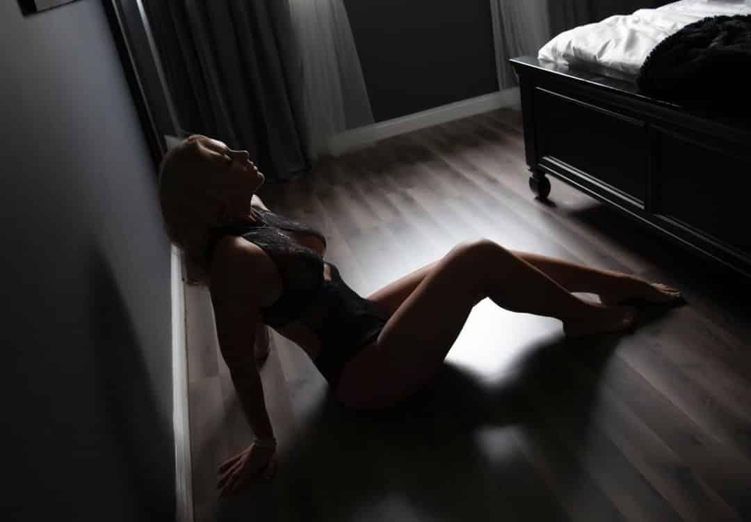 Woman posing on a bedroom floor in black lingerie