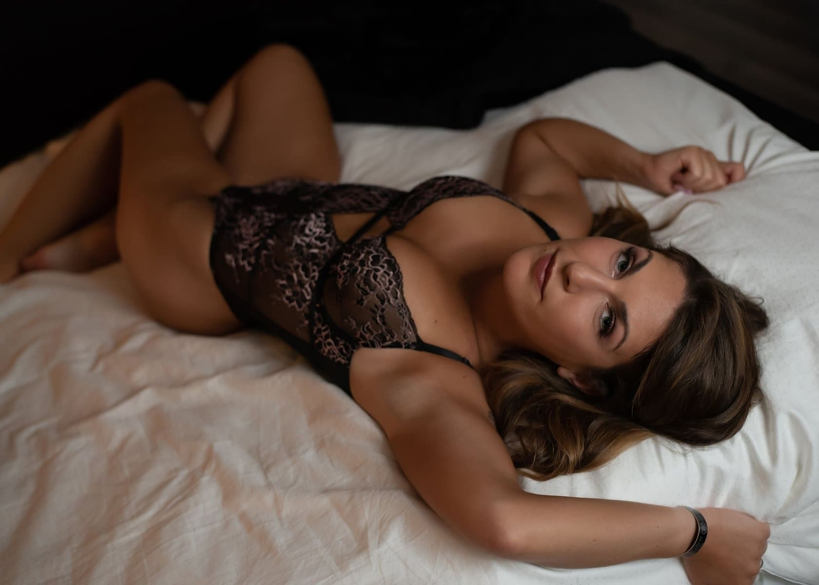 Woman posing on a bed wearing black lingerie