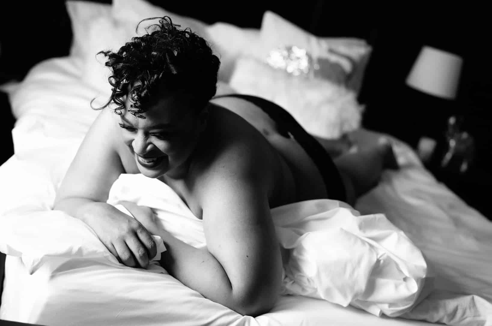 Boudoir black & white photo of a topless woman laying with her stomach down on a bed