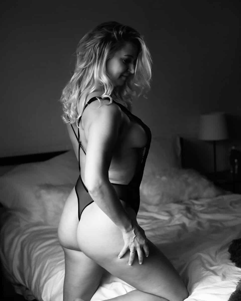 Boudoir black & white photo of a blonde woman standing next to a bed