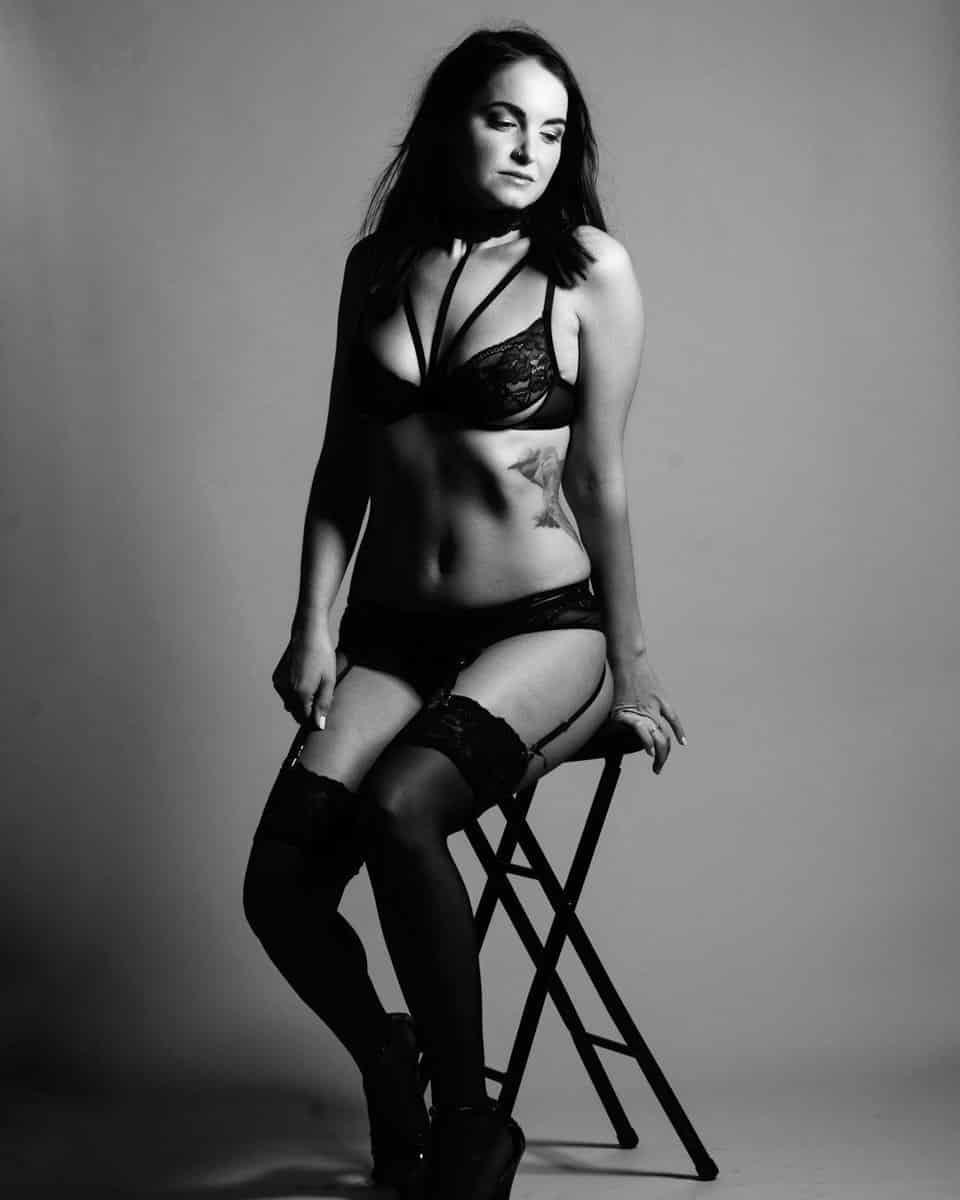 Boudoir black & white photo of a woman sitting on a stool